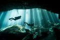 Two divers swim through a cenote in Mexico