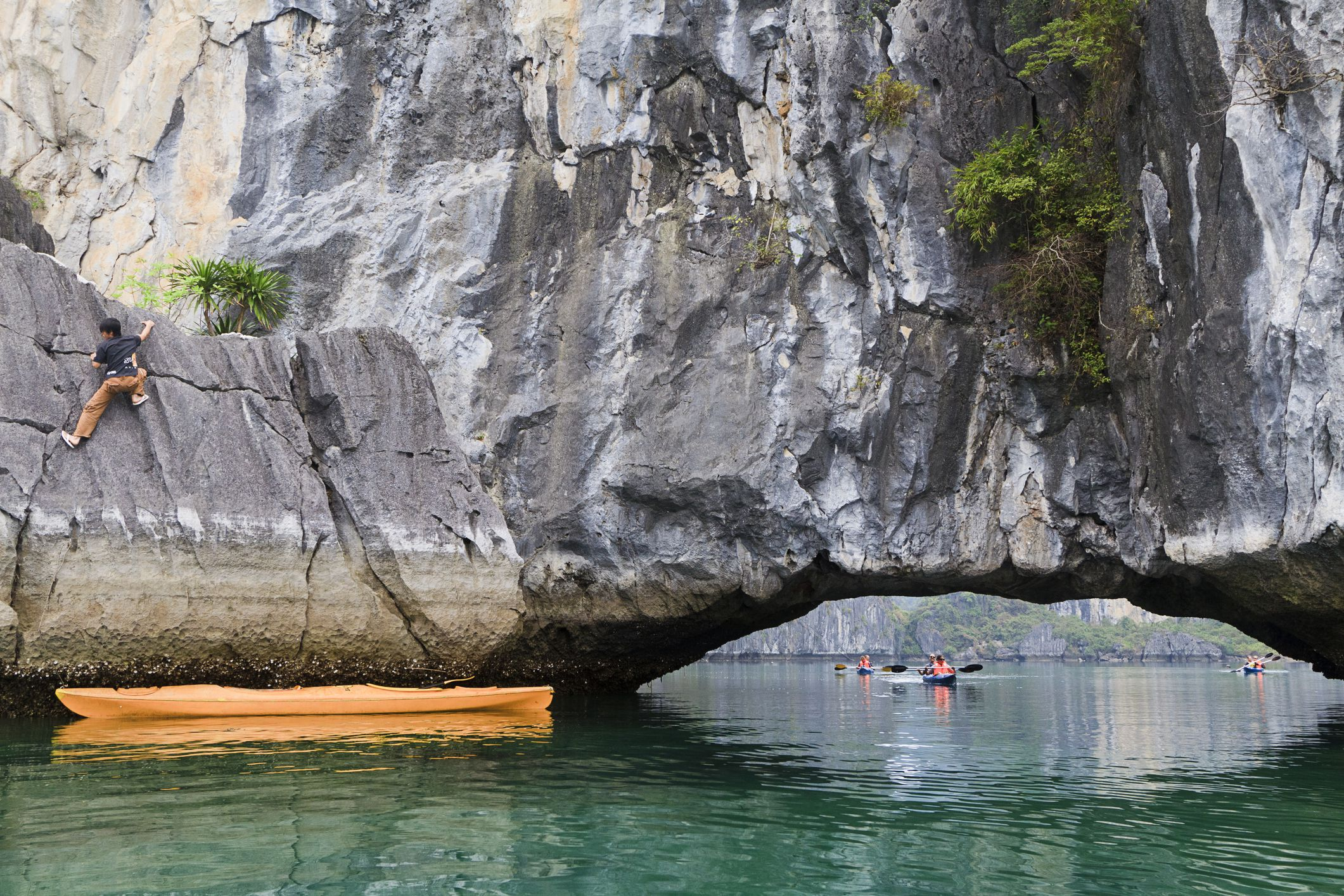 Rock climber and kayakers on Ha Long Bay, Vietnam