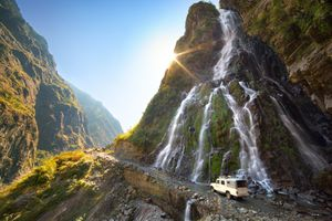 Jeep driving along a dirt mountain road with a small waterfall running down cliff