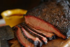 Closed up on partially slice brisket with a knife on a cutting board
