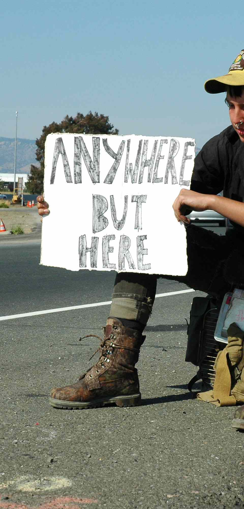 woman by the side of the road with hitchhiking sign