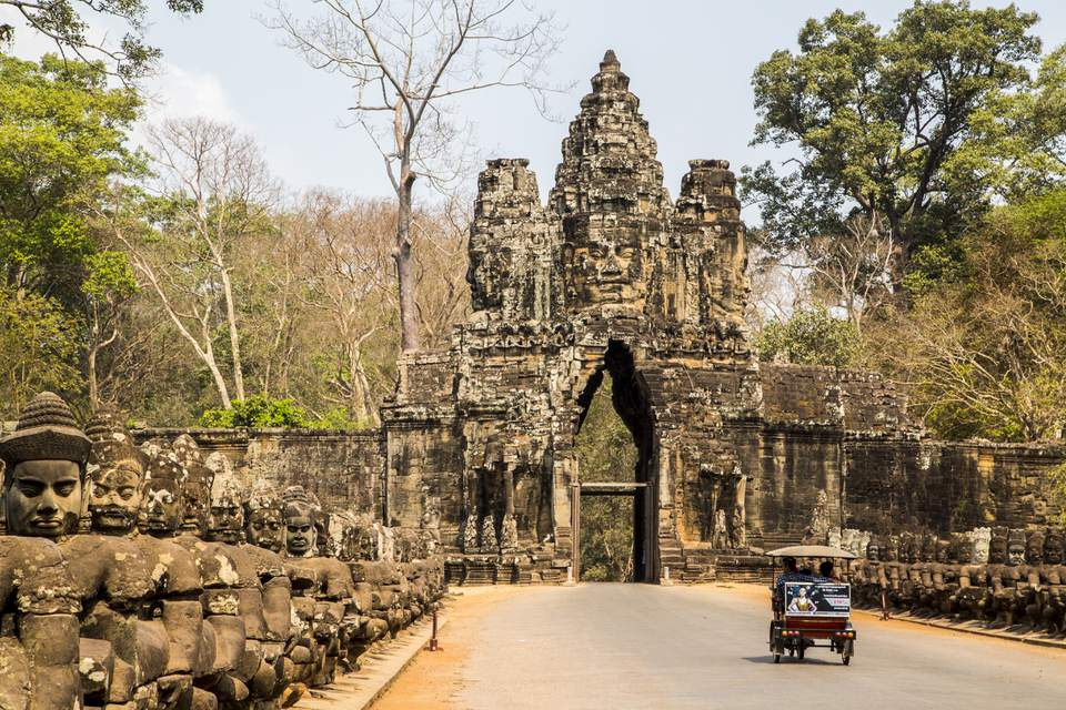 A tuk-tuk driving through gate at Angkor Wat, Cambodia