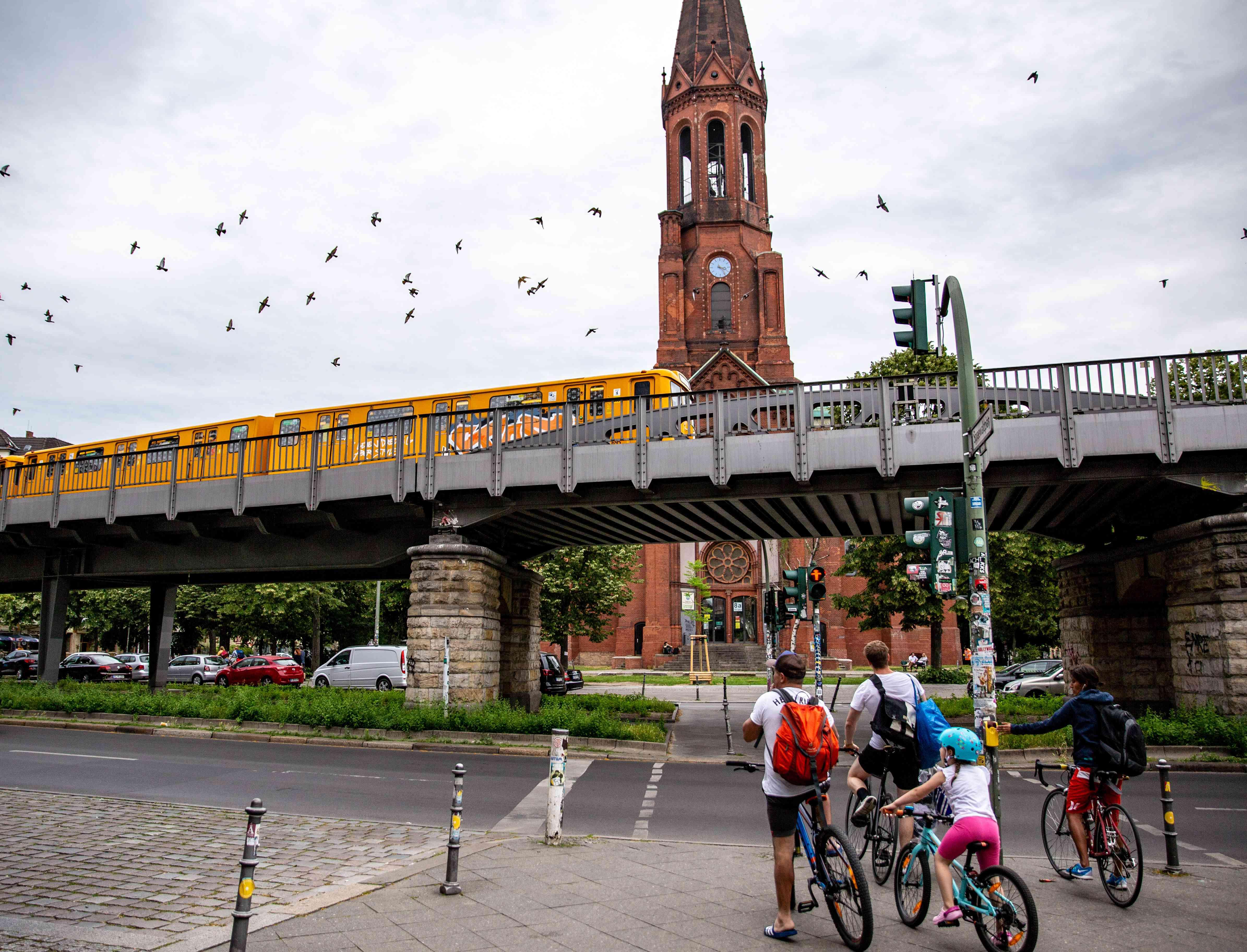 People on a bike watching a graffitied train go by in Kreuzberg
