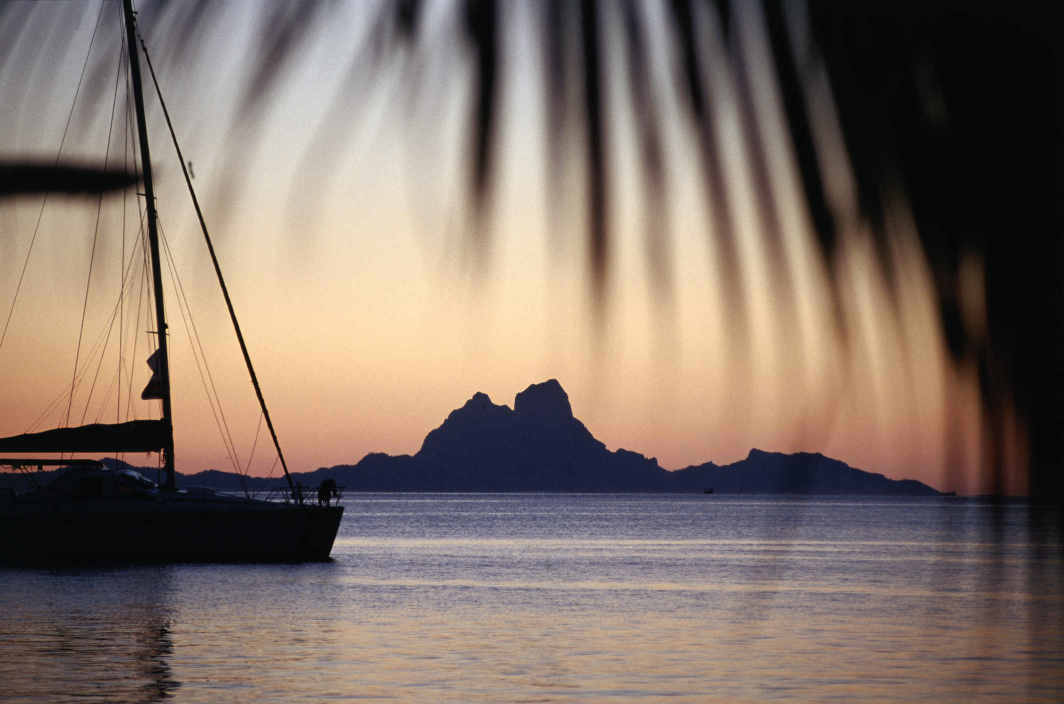 Boat with Bora Bora Island in the distance at sunset.