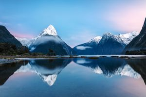 pointed snow-capped mountains reflected in water with blue and pink sky