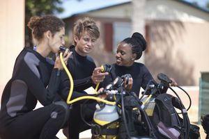 Two young women being taught to scuba dive by an instructor