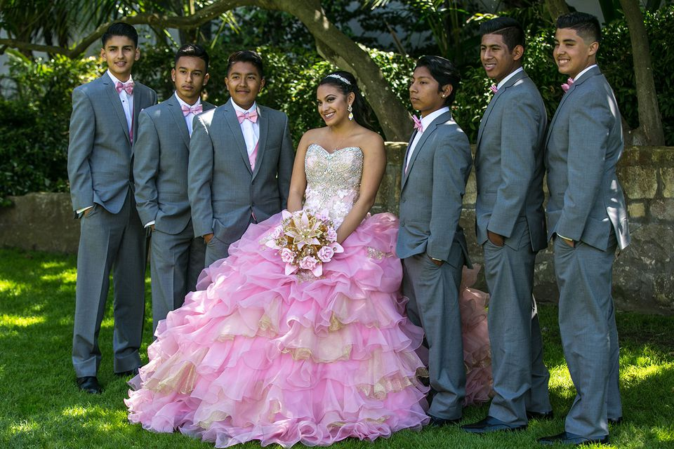 A girl at her 15th birthday—the Quinceañera—stands surrounded by her escorts, or Chambelanes