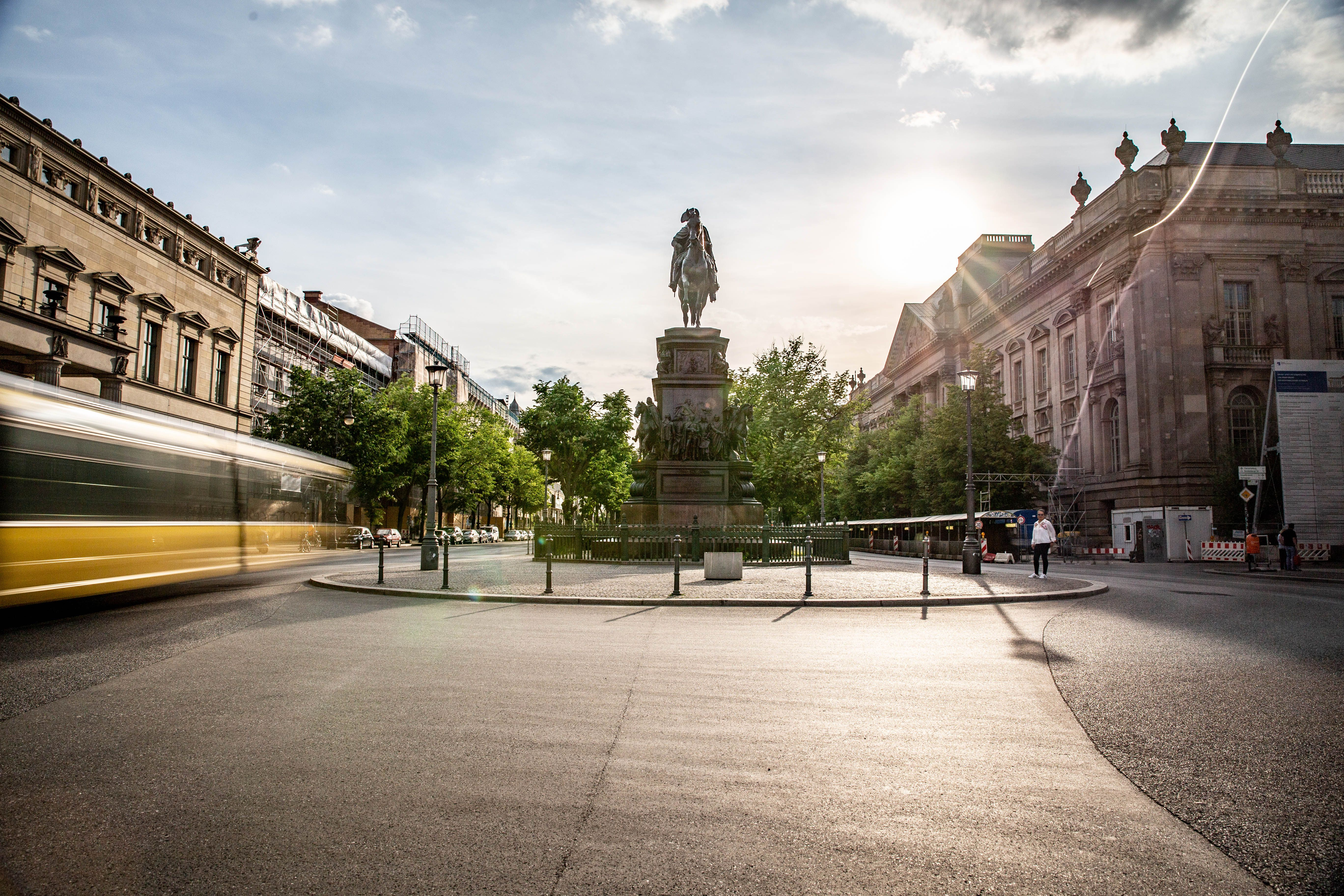 A statue on Unter Den Linden and trams passing by