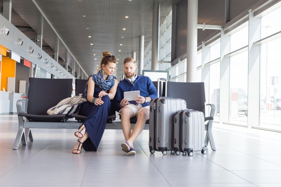 Young couple looking at tablet at airport