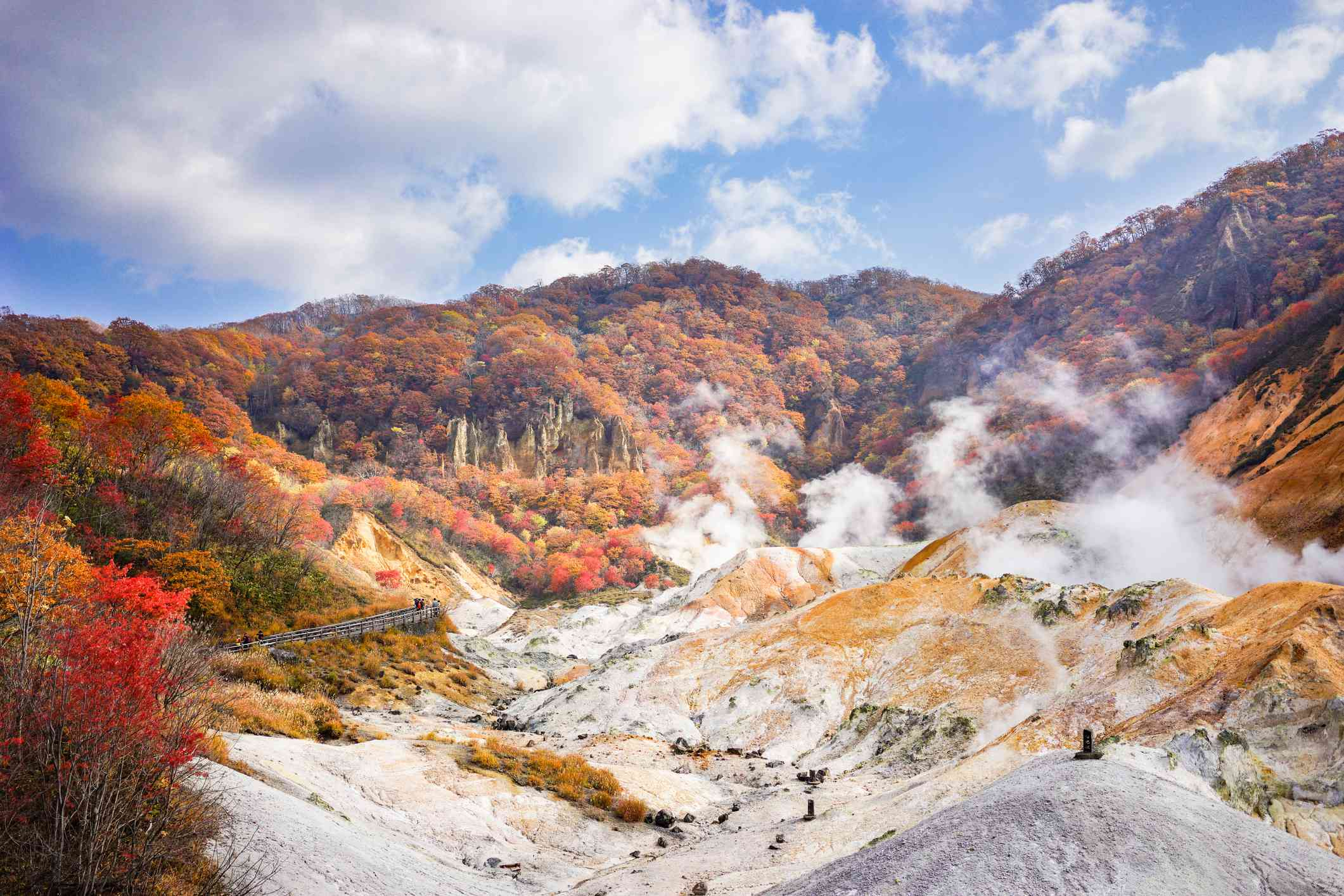 Beautiful sunny day at Noboribetsu Jigokudani or Hell Valley in Hokkaido, Japan. Autumn season, red leaves, blue sky and sulfur gas steaming out from ground.