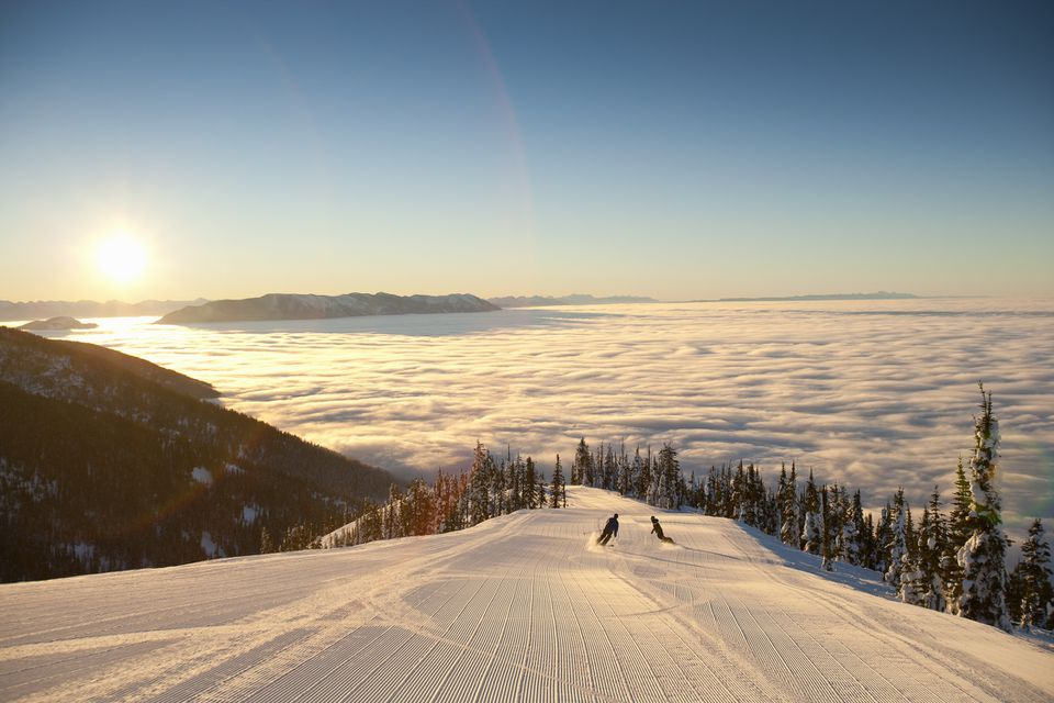 Silhouette of couple skiing above clouds
