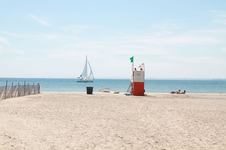 Hanlan's Point Beach in Toronto, with a lifeguard chair and sailboat in the background.