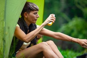 Adult Woman Applying Mosquito Repellent While Camping - stock photo