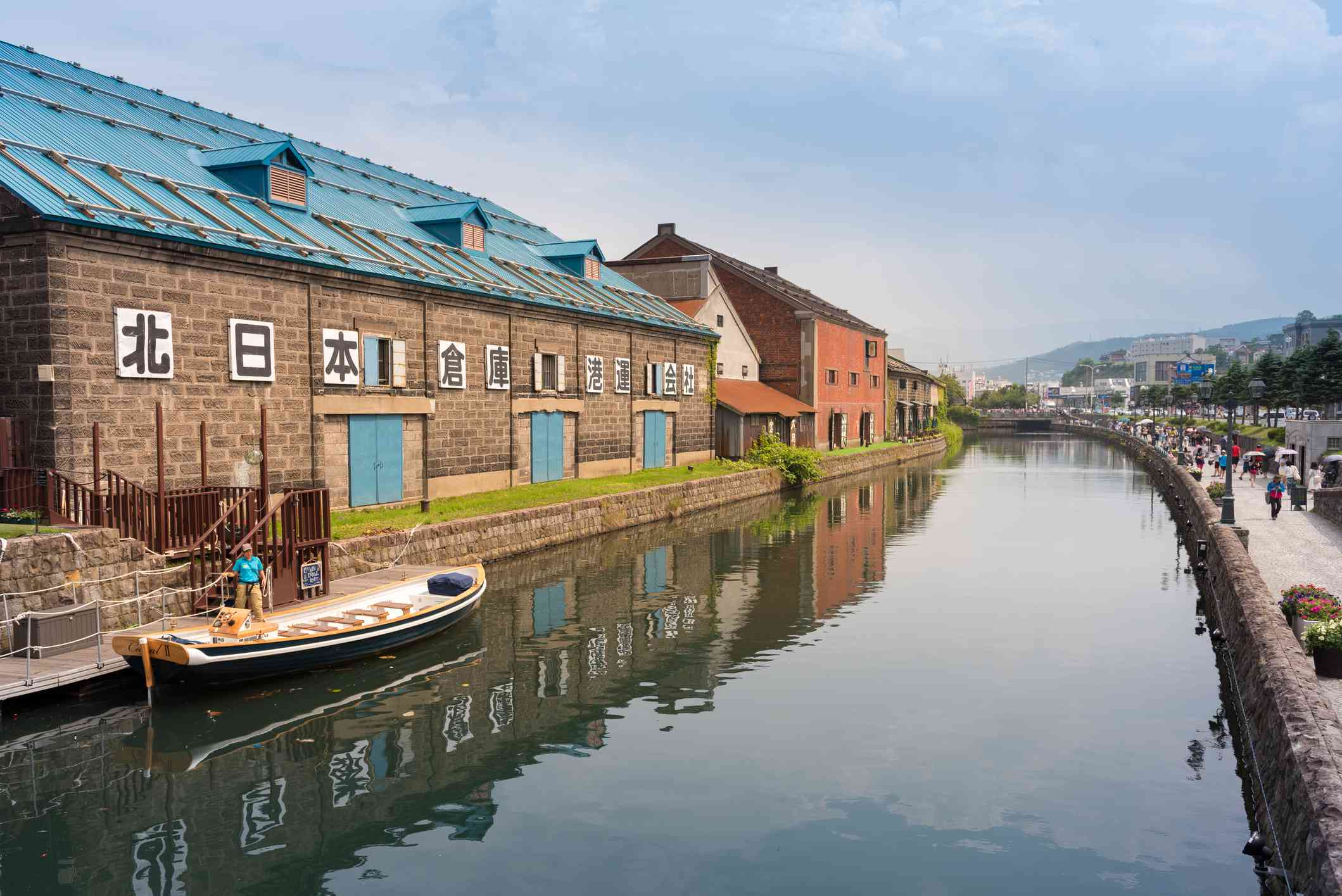 buildings and a lone boat on a canal in Japan