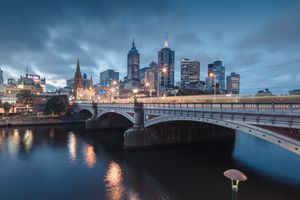 Melbourne, Australia at night with bridge over river and lights illuminating the city skyline at dusk.