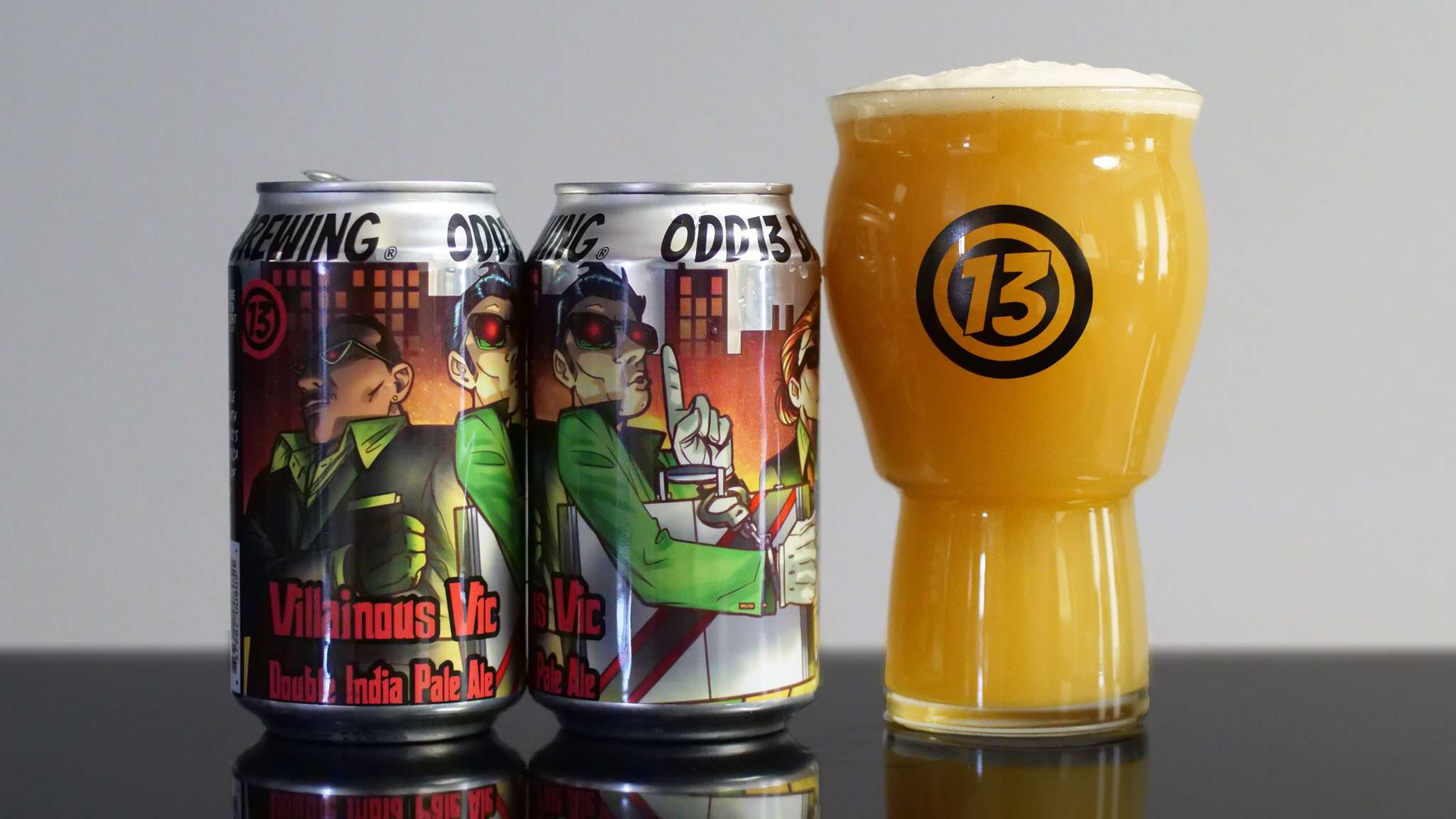 Two colorful beer cans and a Odd13 Brewing branded pint glass
