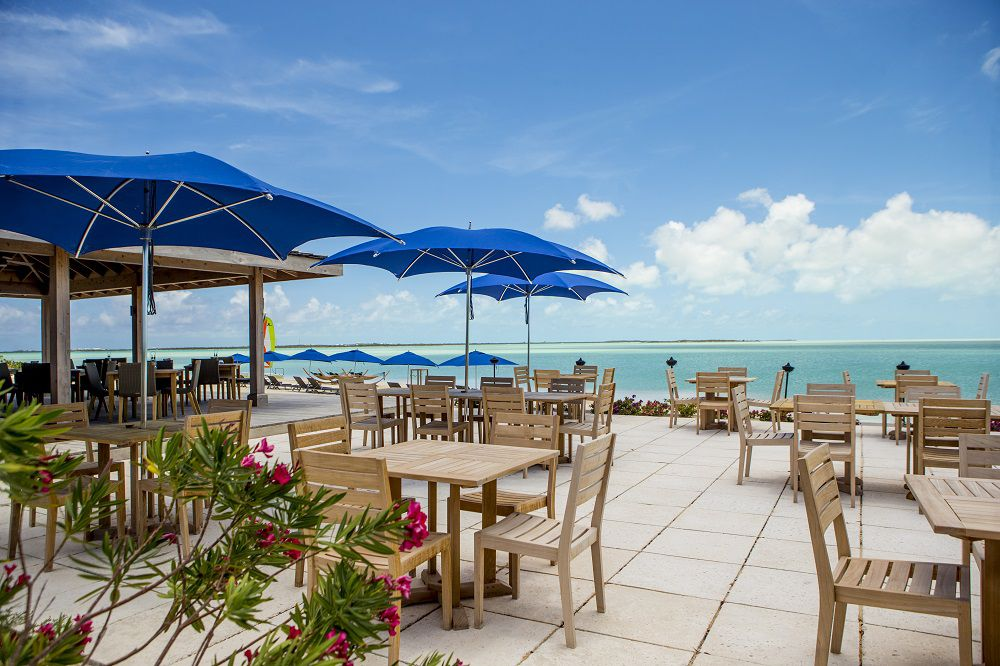 Light-colored wooden outdoor dining tables with blue umbrellas and the ocean in the background