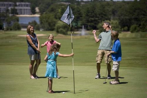 two adults and three children golfing
