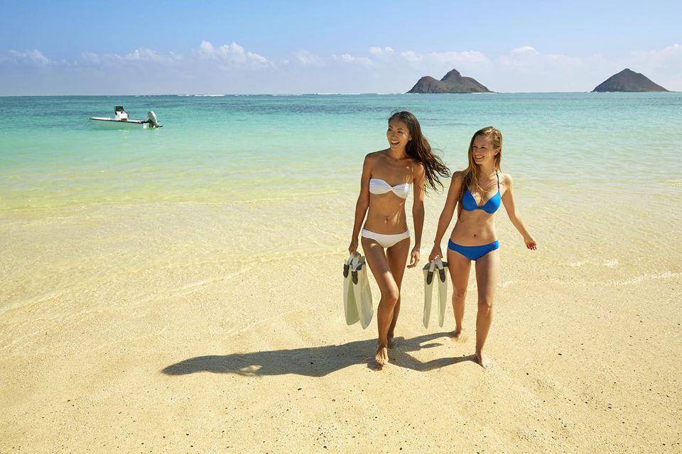 Women Carrying Snorkel Fins On Beach