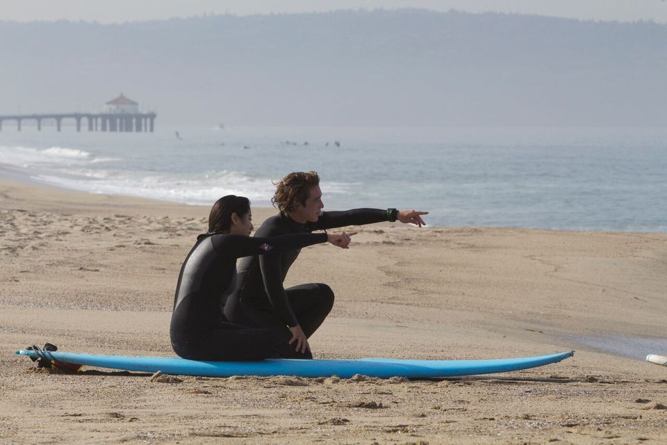 Two people with surfboards on Manhattan Beach in Los Angeles, California.