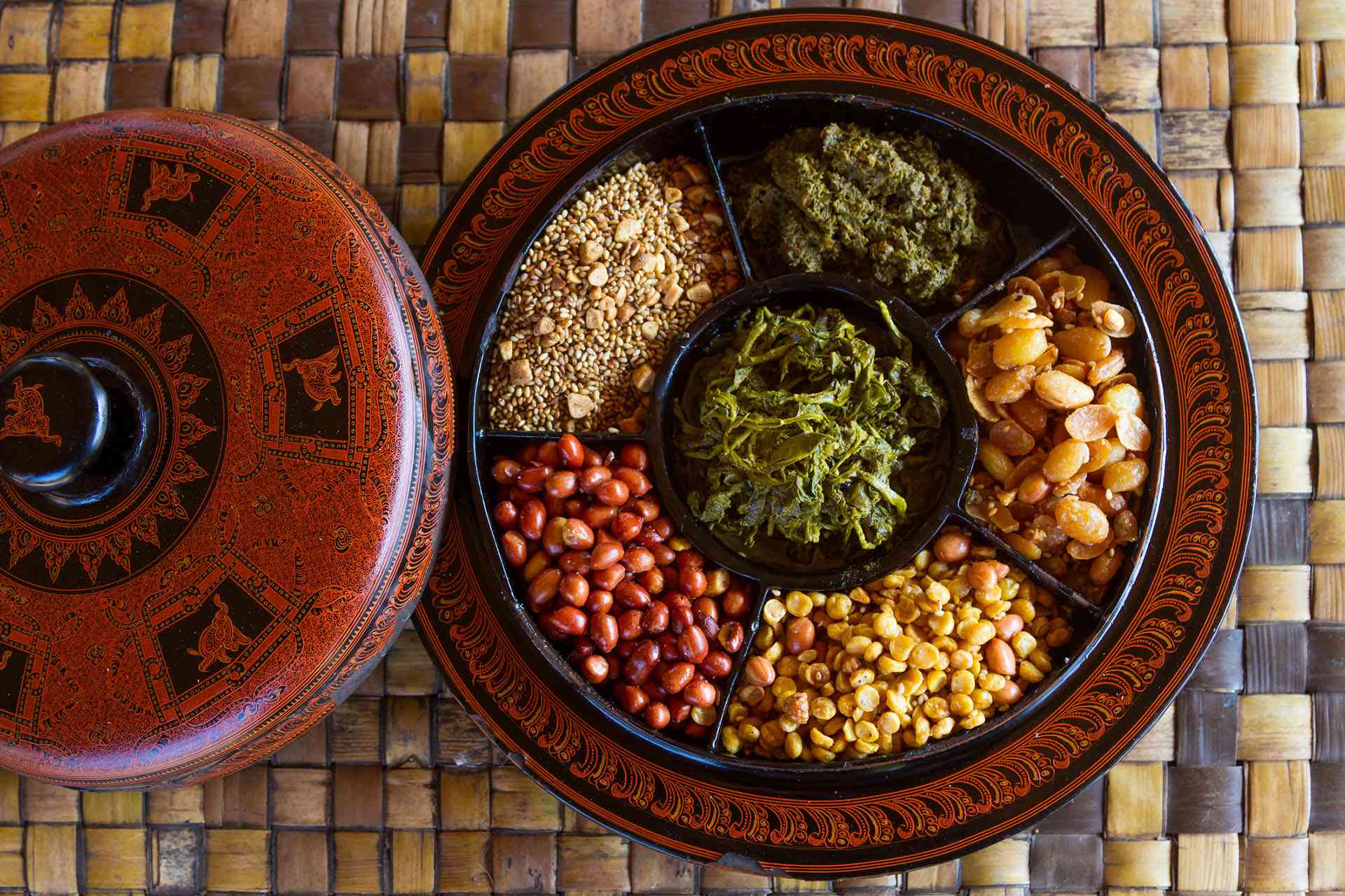 sectioned round plate with fermented tea leaves, and assorted nuts