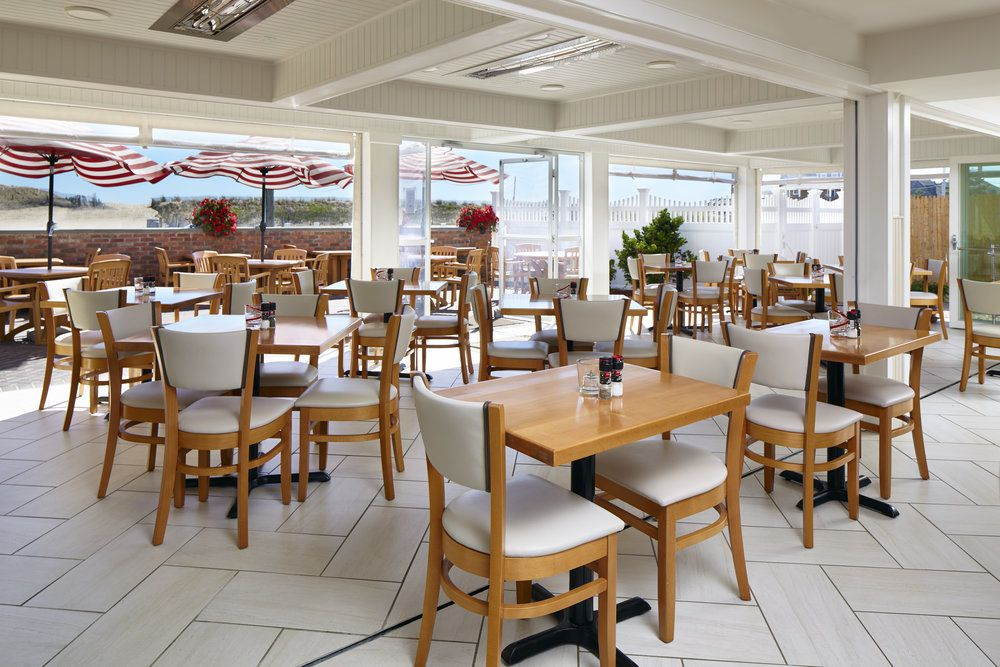 White chairs and light brown, wooden tables at Maria's Seaside Cafe