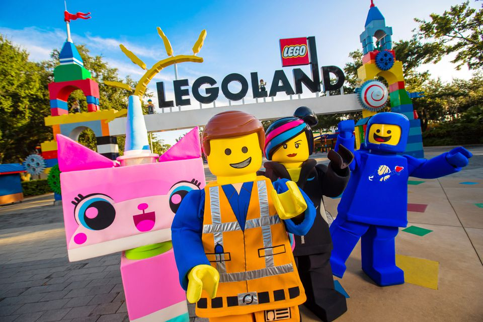"""four life-size characters from """"The Lego Movie"""" posing for a picture at the entrance to Legoland"""