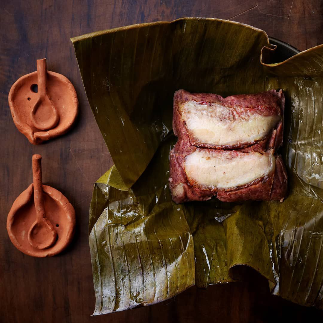 A tamale using traditional ingredients on a banana leaf