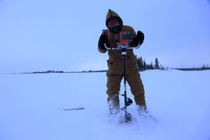 A man using a power auger to drilling a hole on the frozen Great Slave Lake for ice fishing.