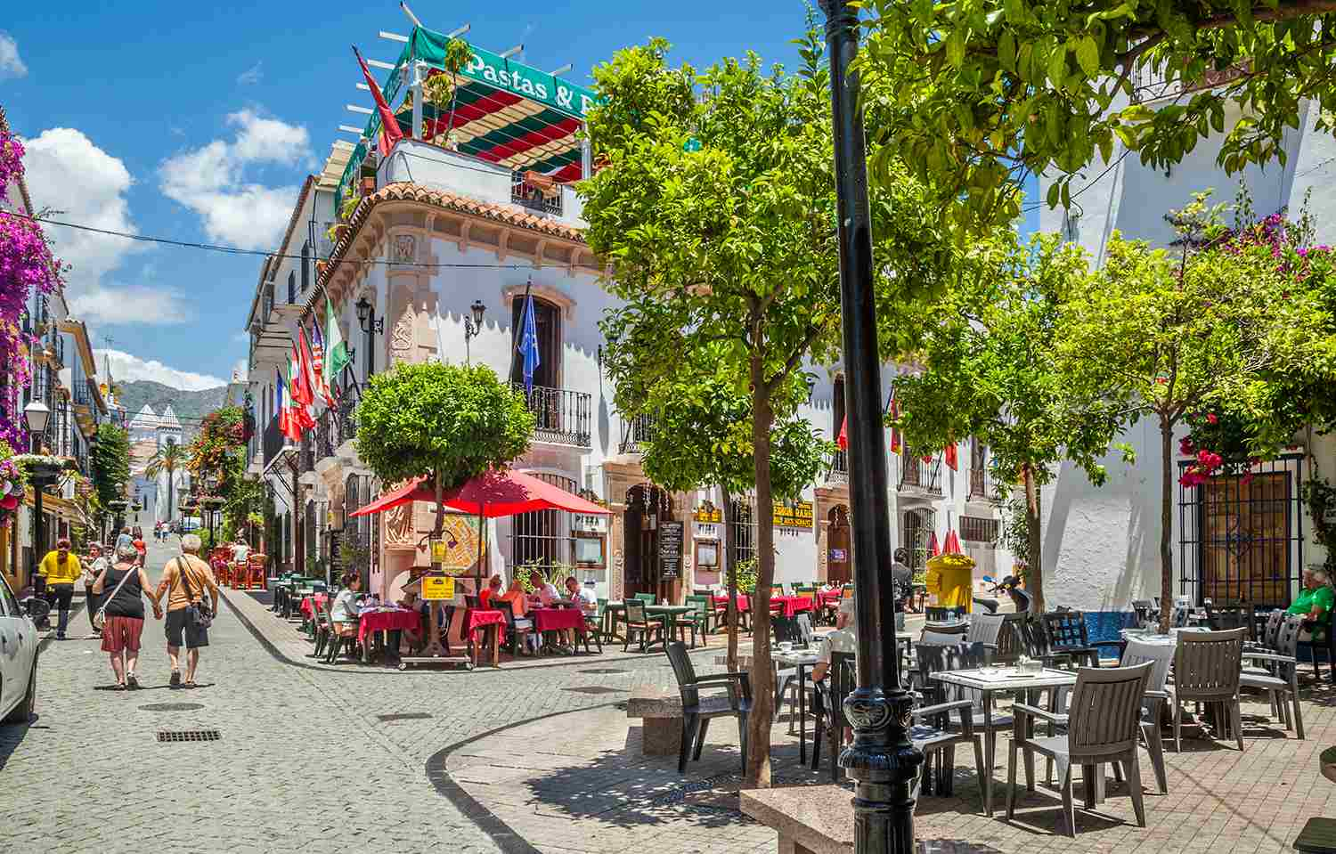 People walking down a restaurant-lined street in Old Town Marbella