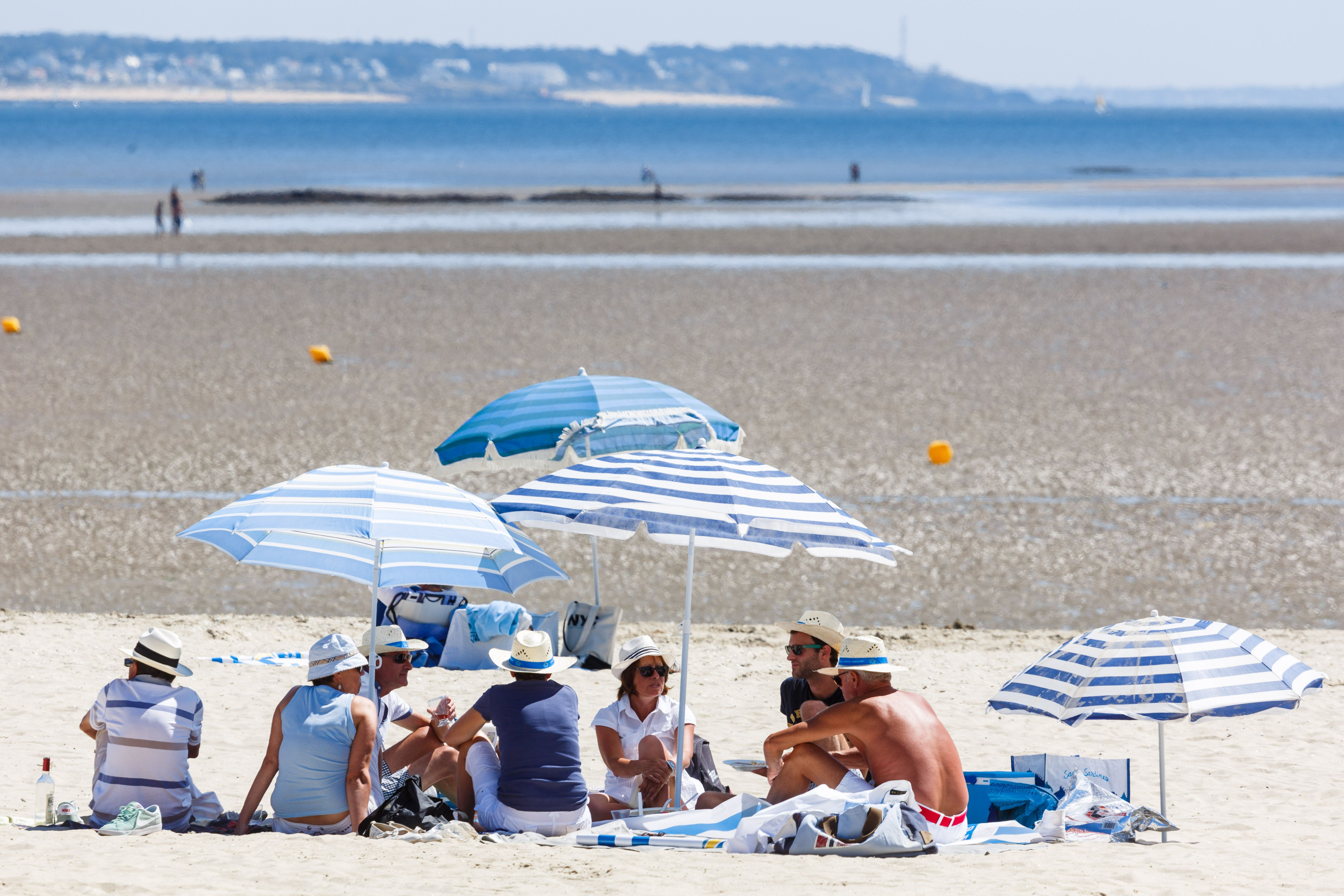 Beachgoers gathered beneath blue-and-white-striped umbrellas at La Baule-Escoublac, Brittany