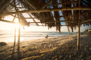 A picture from inside a beach bungalow of a surfer walking along the beach and the sun setting in the background