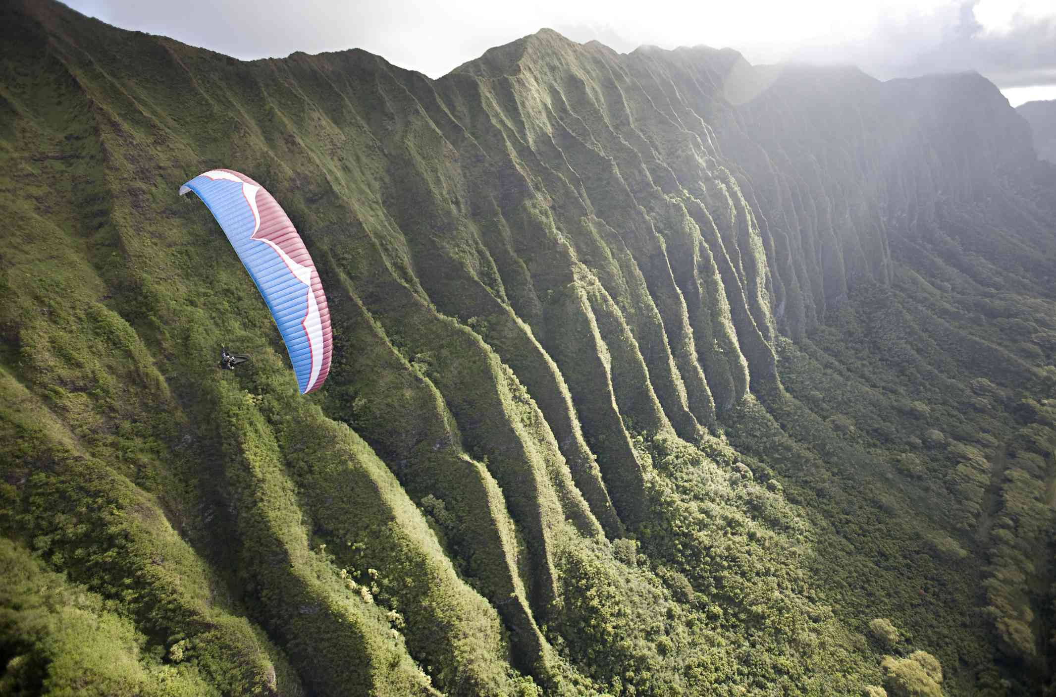 folded green cliffs with blue and red paraglider in foreground