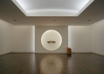 Empty room with white walls,, recessed ceiling, and hard wood floors. on the room's back wall there is a wall with a circular cut out. inside the circle is a small shelf with three bottles on it. There is alos a basket with three orange towels in it on the back wall