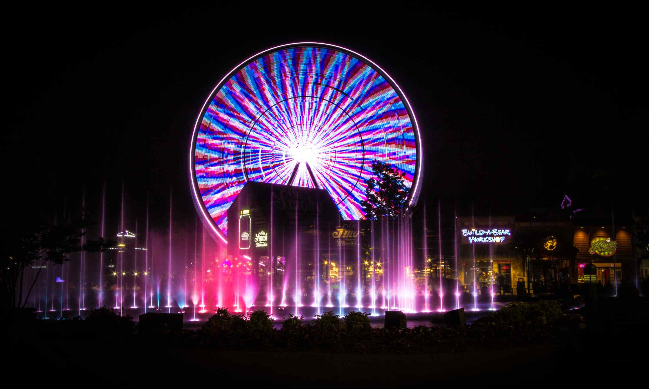 Illuminated fountains, shops and Ferris wheel at the Island entertainment complex in the Smoky Mountain resort town of Pigeon Forge, Tennessee