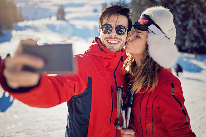Young couple is taking selfie/making video call on the ski slope