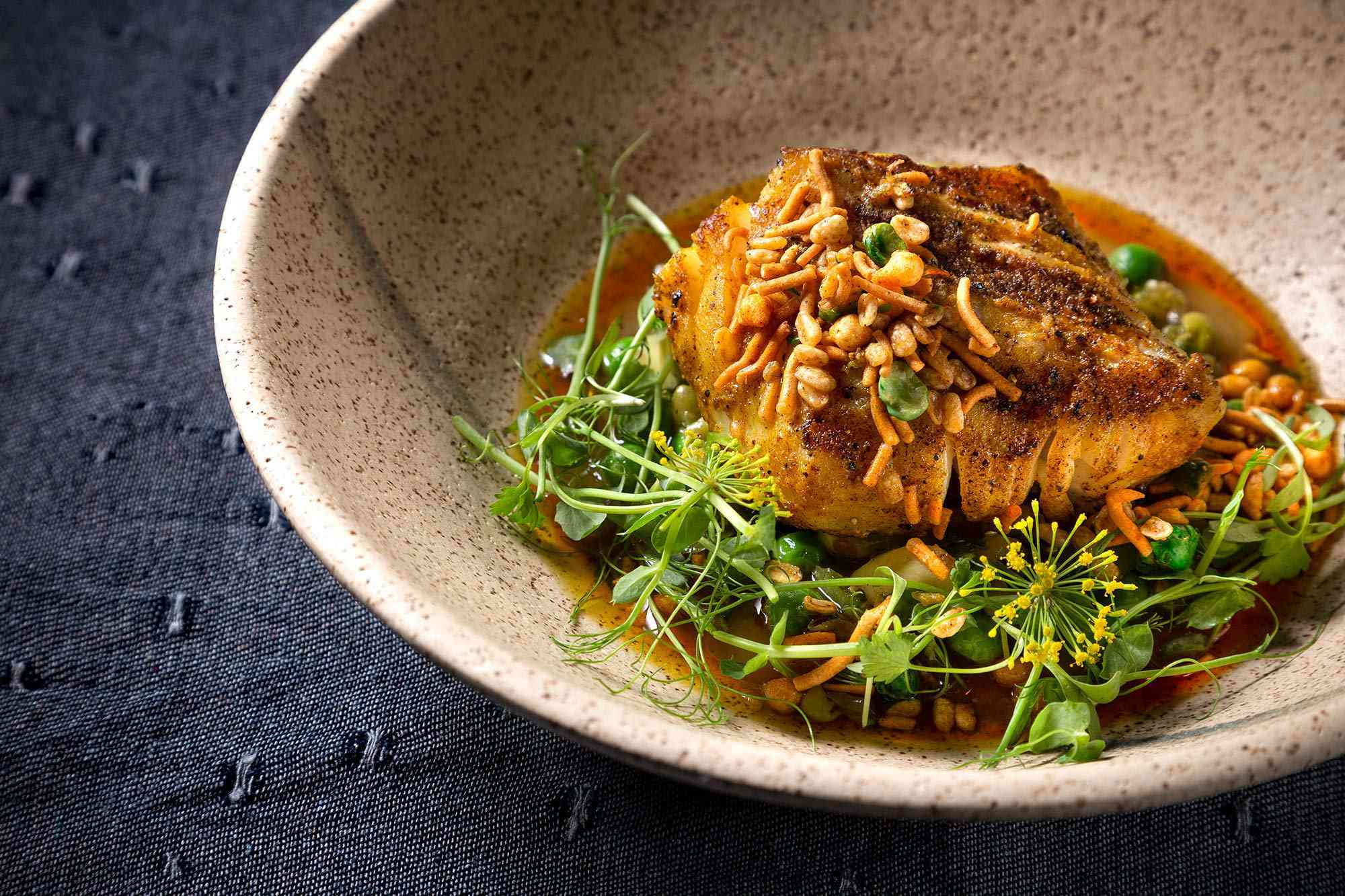 Grilled cod in a stone bowl garnished with green sprouts