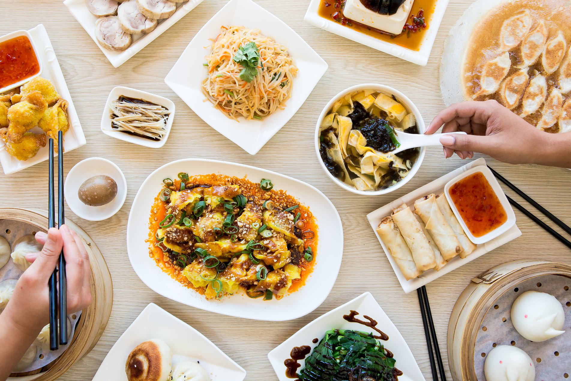 Aerial shot of share plates of dumplings and noodles at Authentic Bites