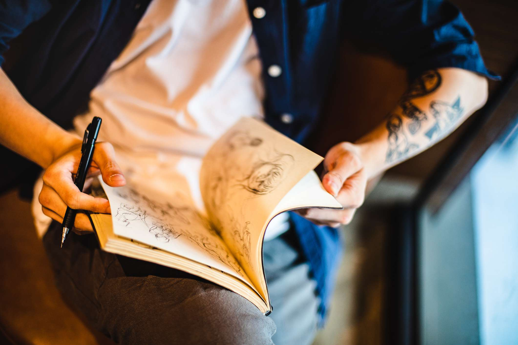 Asian young man sitting and doing a sketch on a notebook