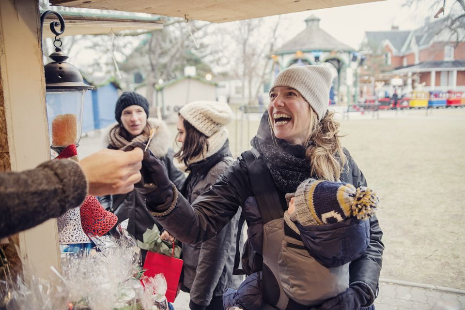 Woman tasting product at an outdoors public market in winter.
