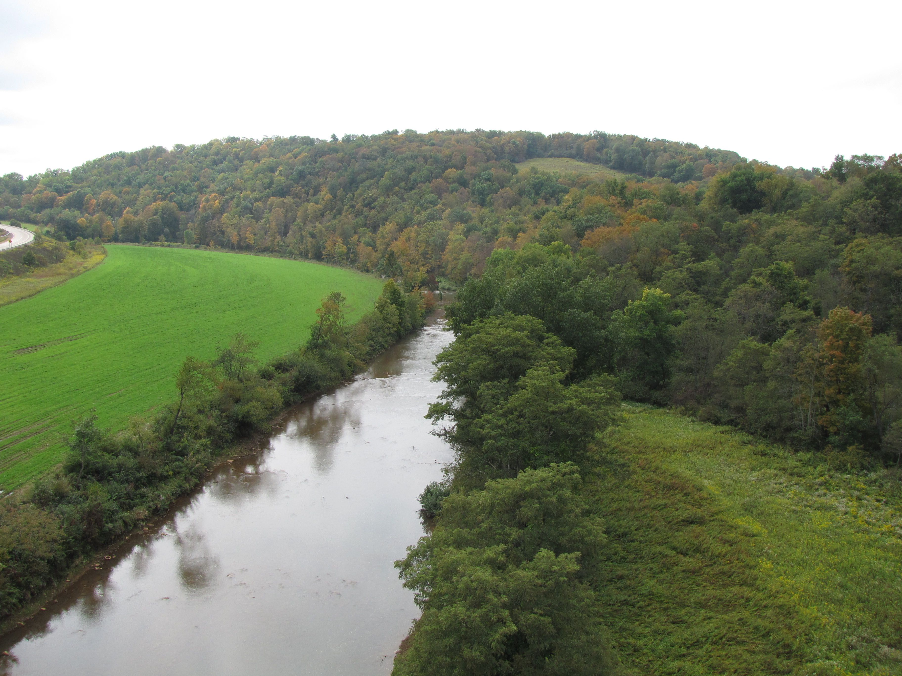 View from above of canal running through field of trees in autumn at Chesapeake and Ohio Canal National Historic Park