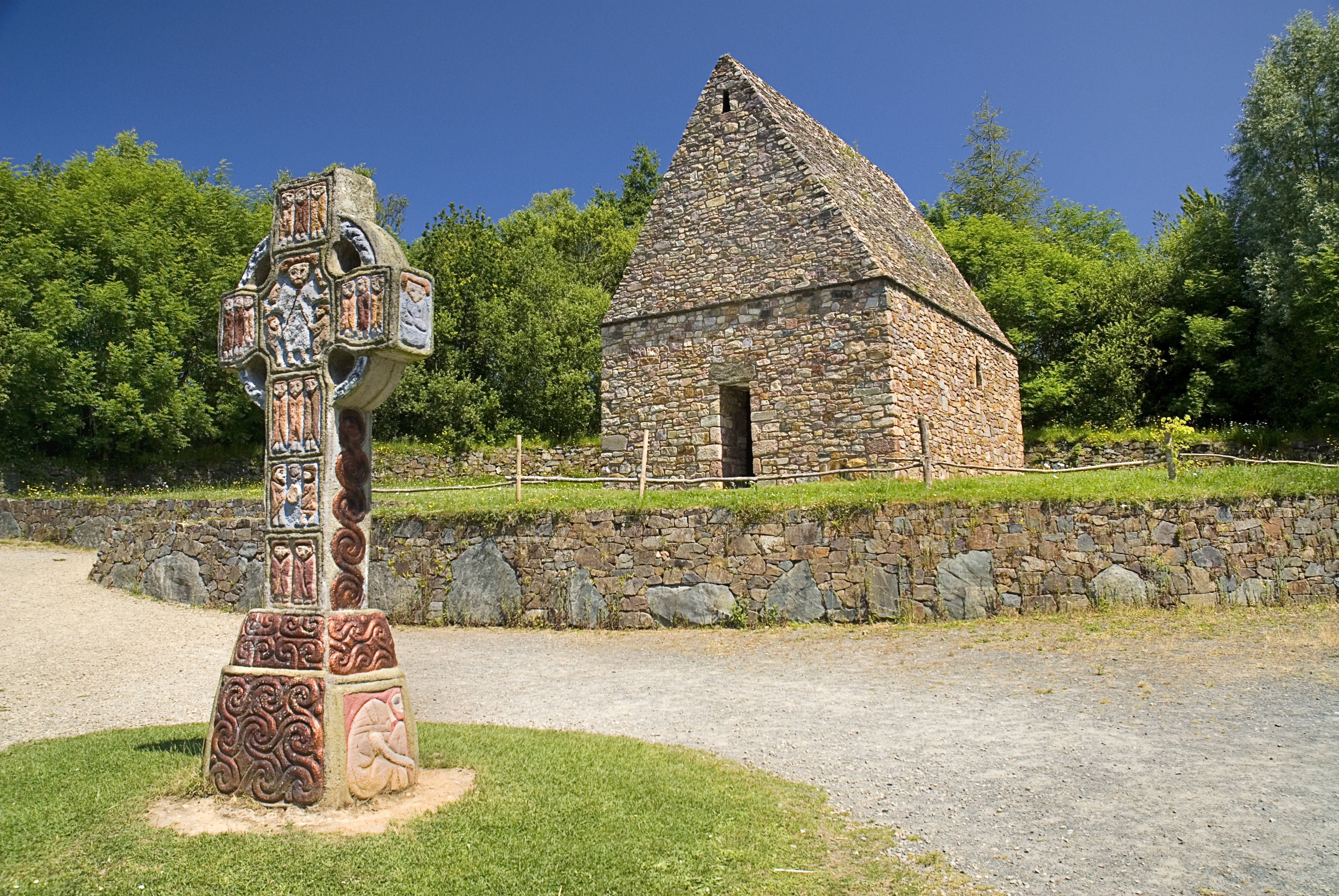 IRELAND, County Wexford, Irish National Heritage Park, Reconstruction of a typical monastic oratory with replica of a celtic cross in front.