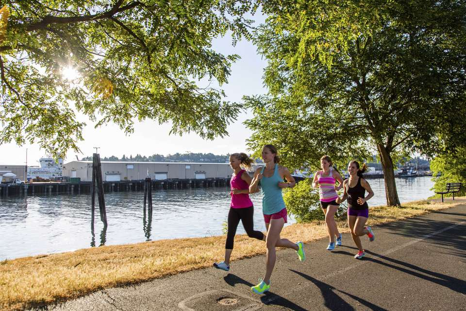 Four young women jogging together along coastal park, Seattle, Washington, USA