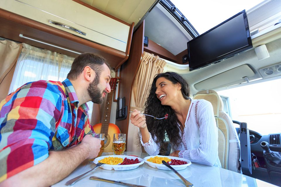 Cheerful young couple eating inside of an RV equipped with a TV