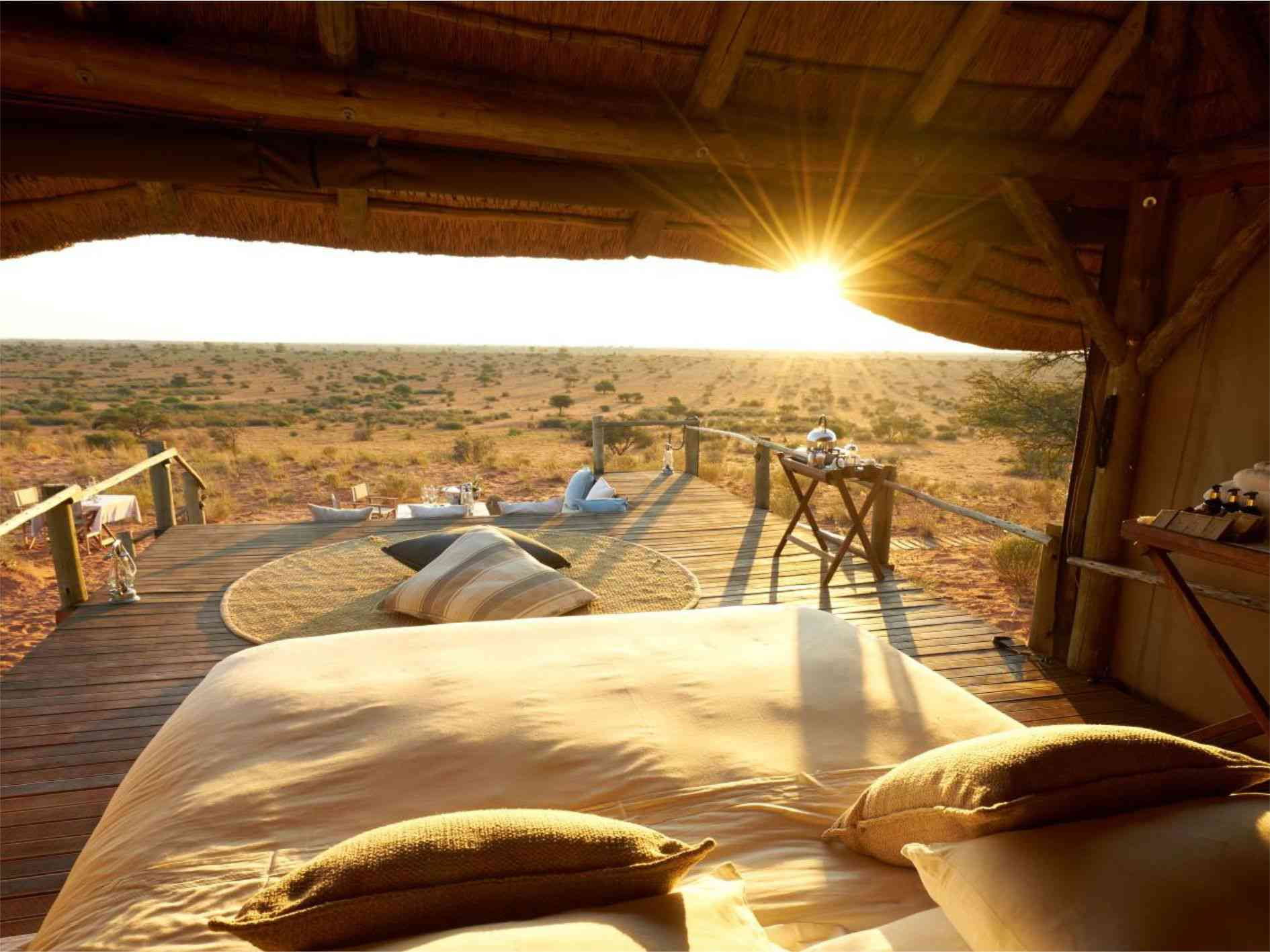 View from inside a room at Tsuwalu looking out on the savannah. There is a white bed and the sun is setting