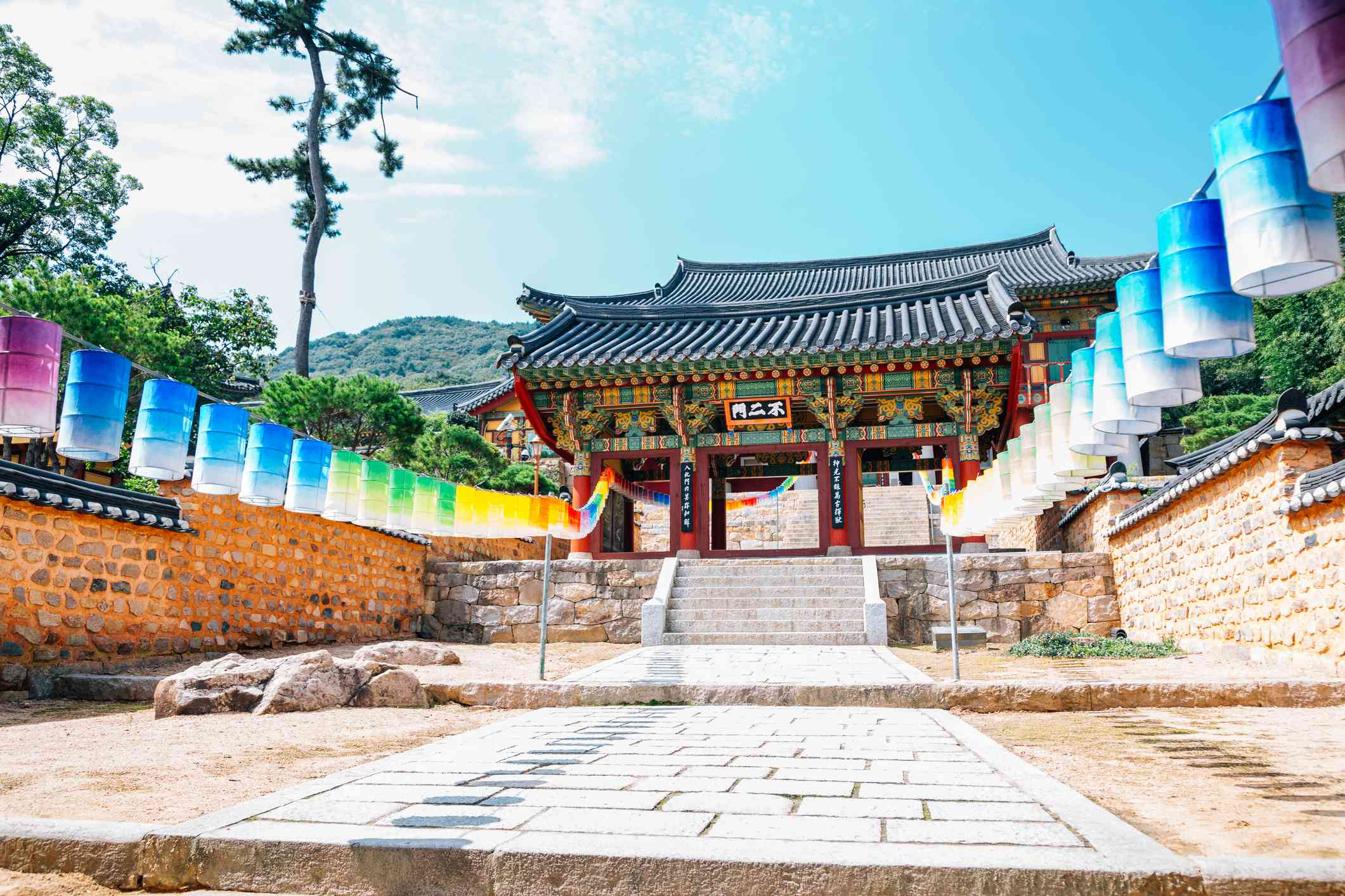 Colorful lanterns on either side of an walkway leading to a red Korean Temple gate