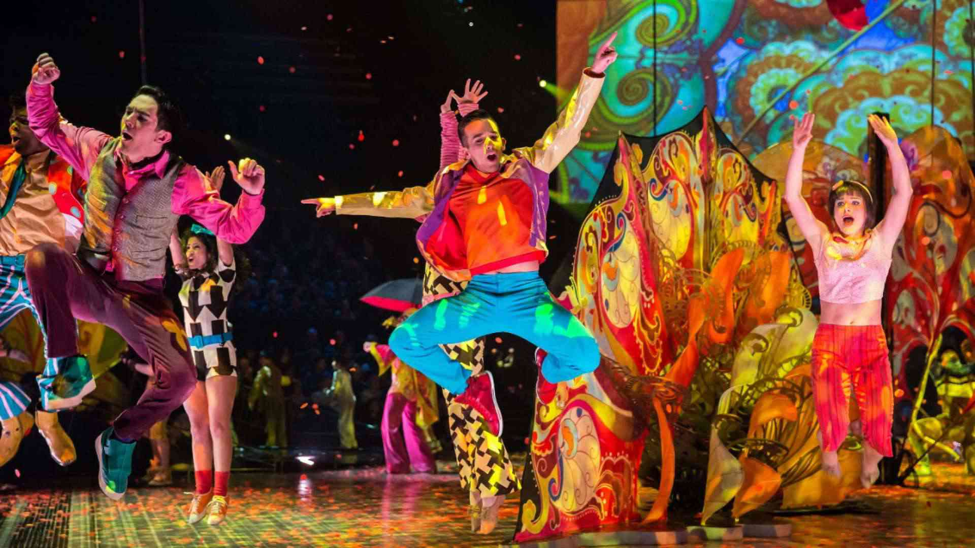 Dancers jump in the air on a colorful background