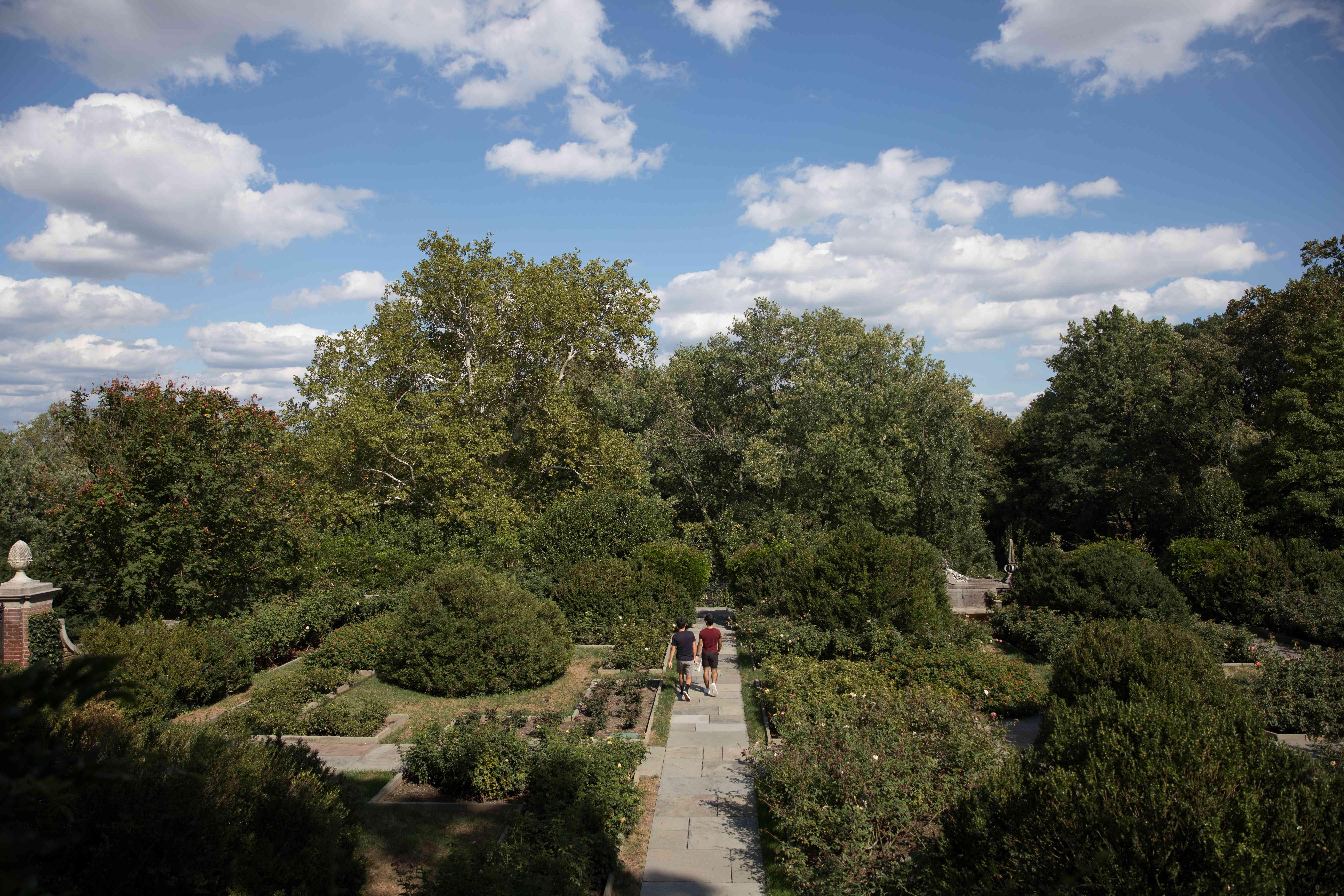 Two people walking through the gardens at Dumbarton Oaks