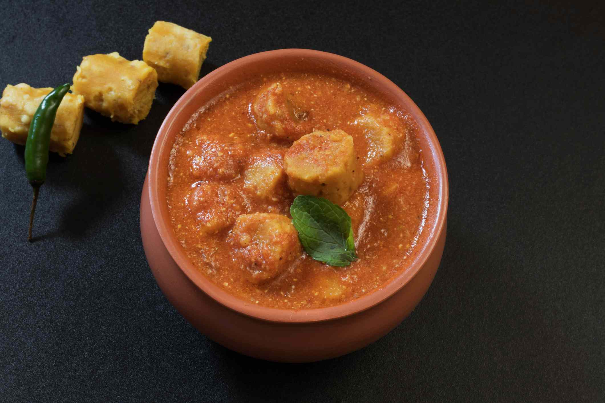 bowl of red curry with chickpea dumplings