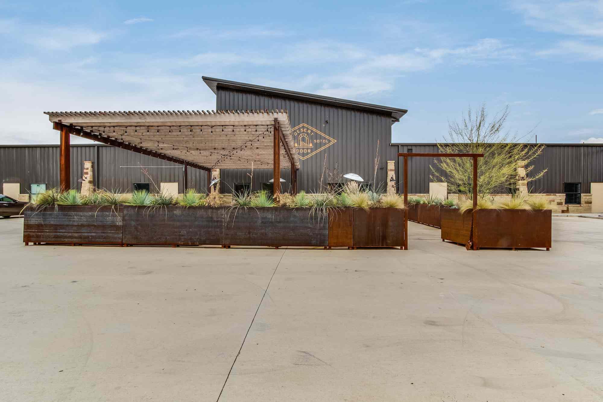 Industrial main building and patio seating at Desert Door Distillery